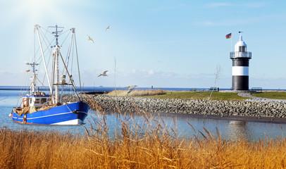 Krabbenkutter auf dem Heimweg, Kutterhafen mit Wremen mit Leuchtturm an der Wurster Nordseeküste