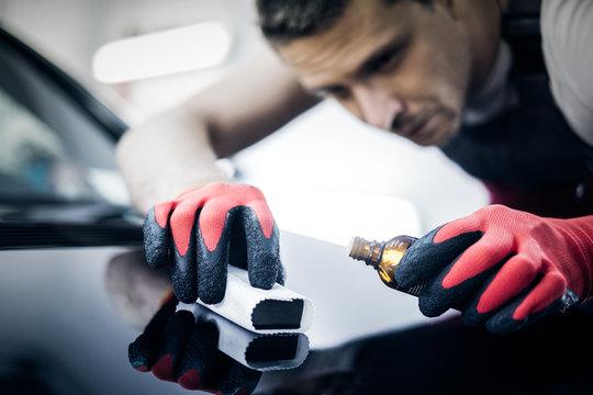Worker on a car wash applying nano coating on a bonnet.