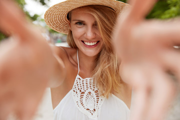 Close up shot of pleased smiling woman stretches hands for embracing you, enjoys good summer day outdoor, dressed in fashionable dress and hat, recreats in resort country. Vacation and people