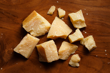 Pieces of parmesan or parmigiano reggiano cheese on a wooden board. Parmesan cheese uses in pasta, risotto and salads. Top view.