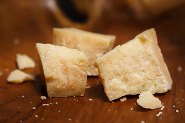 Pieces of parmesan or parmigiano reggiano cheese on a wooden board. Parmesan cheese uses in pasta, risotto and salads. Close-up.
