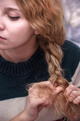 beautiful girl ties her hair in pigtails