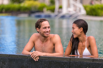 Pool couple relaxing on luxury resort travel holiday talking together on summer vacation. Asian woman, caucasian man in love.