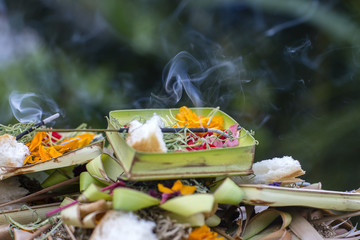 Burning incense sticks surrounded with Balinese offerings outside on a hindu temple in Ubud, Bali, Indonesia.