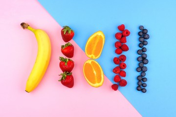 Fruit arrangement over a modern pink and blue background with banana, strawberries, oranges,...