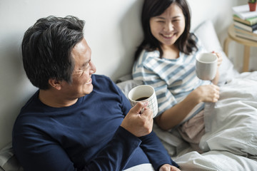 Asian couple drinking coffee in bed