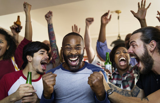 Frieds cheering sport at bar together
