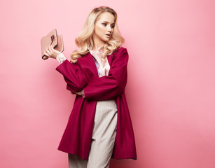 Beautiful blond woman in a blouse and pants wearing glasses, holding handbag posing over pink background.
