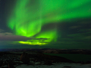 Northern Lights, polar lights above the hills and tundra bay in winter.