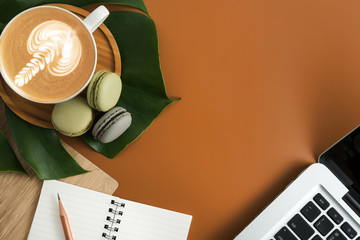 Styled stock photography brown office desk table with blank notebook, computer, supplies and coffee cup. Top view with copy space. Flat lay.