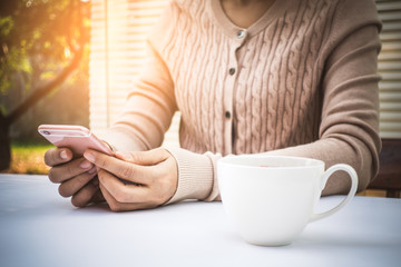 Woman's hand is holding and touching a smartphone on white office desktop.