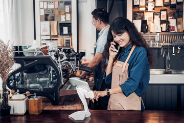 Asia Barista waiter use tablet take order from customer in coffee shop,cafe owner writing drink order at counter bar,Food and drink business concept,Service mind concept.restaurant worker.