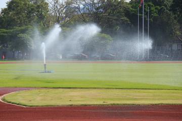 Sprinklers spraying water on grass
