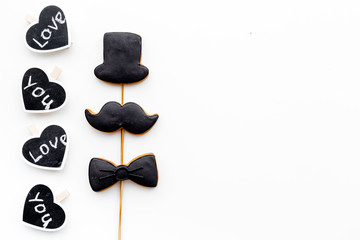 Men's birthday concept. Cookies in shape of moustache, hat, bow tie. Hearts with lettering love you on white background top view copy space