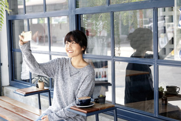 Asian women making selfie at cafe by her smartphone. Urban life concept.