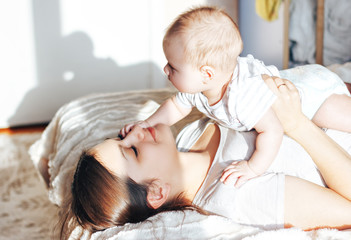 Young mother playing with her baby on bed, laughing