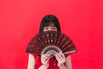 Young Asian woman holding a Chinese traditional style fan isolated over red background. Chinese new year and Spring festival concept can be applied