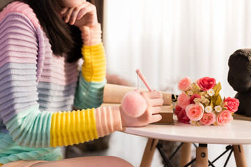 Close-up of Young woman in colorful fashionable sweater writing a diary and drawing in the book.