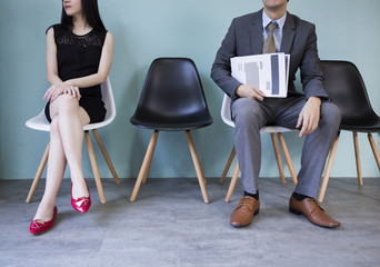 Close up of business man and business woman holding a blank and empty document paper waiting to be interviewed in the job recruitment processing.