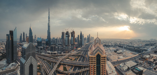 Aerial view over big highway interchange and skyscrapers in Dubai, UAE, at sunset. Scenic panoramic cityscape. Colorful travel and architectural background.