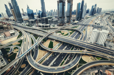 Aerial view of big highway interchange with traffic in Dubai, UAE, at day. Scenic cityscape. Colorful transportation, communications and driving background.