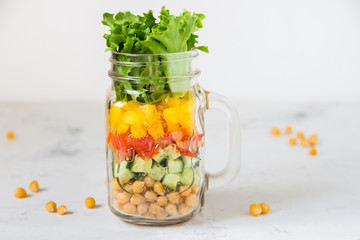 Salad in a jar. Homemade healthy salad from chickpea, tomato, yellow paprika, cucumber and green lettuce