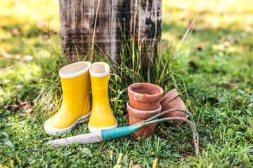 Hoe, wellington boots and flower pots in the garden.