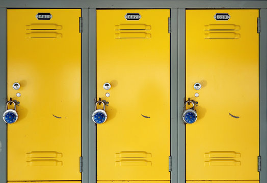 Yellow school lockers with locks - Three locker doors of three yellow lockers in the hallway of a school, each with number plates, and a stainless steel combination lock with a blue knob on the face.