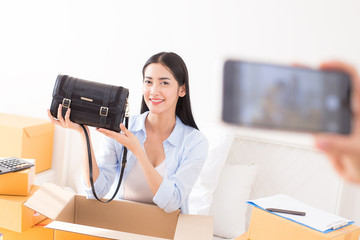 Young Asian Woman using smartphone for promote online business, Young Owner Woman Start up for Business Online. People with online shopping SME entrepreneur or freelance working concept.