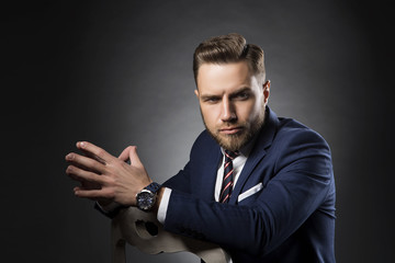 Portrait of young handsome man with beard and hairstyle wearing suit, tie and watch. Dark studio background
