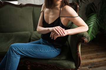 Fototapeta Female hands with a nude manicure. A young thin girl in a black T-shirt and blue jeans is sitting on the green sofa.