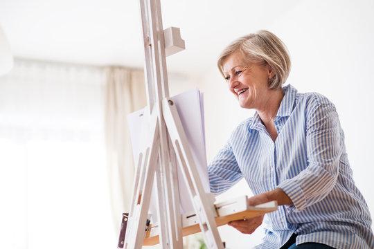 A senior woman painting at home.