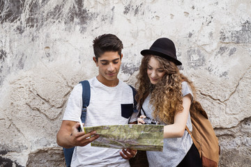 Two young tourists with a map in the old town.