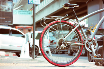 """Bicycle at parking space with background traffic steet in the city at """"Sukumwit"""" BangkokThailand."""