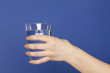 Female hand holding a glass of water on blue background