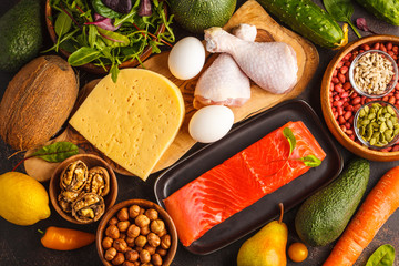Keto (ketogenic) diet concept. Balanced low-carb food background. High protein food. Vegetables, fish, meat, cheese, nuts on a dark background.