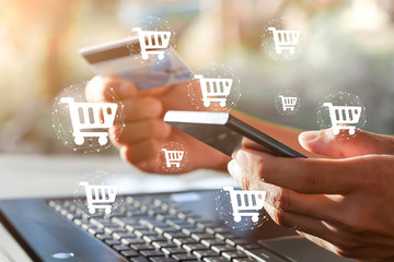 Shopping icons with businessman holding smartphone,Credit Card and Laptops in background. Online shopping or e-commerce concept.