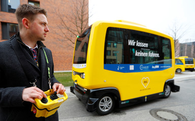 DVB staff member poses for pictures in front of a self-driving shuttle bus, operated by the university hospital Charite and public transport company BVG, during a presentation to the media at the Charite Campus in Berlin
