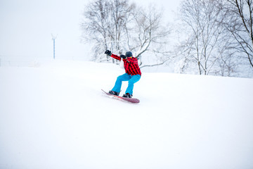 Image of snowboarder man riding snowy hill