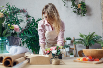 Picture of florist composing bouquet at table on background of flowers
