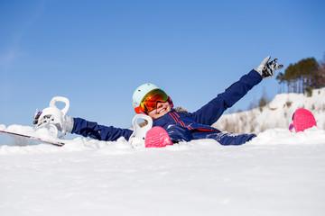 Image of athlete woman in helmet lying in snowdrift