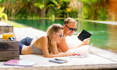 Couple with computers relaxing in sofa by the pool