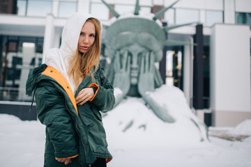 Portrait of blonde in hood and jacket against background of building