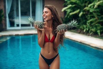 Amazing Brunette Girl In Swimsuit With Pineapple Her Hands Fruit Shows Tongue And Smiles