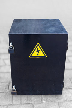 Metal safe box with two padlocks and yellow electricity danger sign on pavement floor, with clipping path.