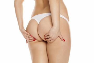 young woman holding her bottom on a white background