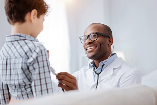Purpose of auscultation. Jovial pleased male doctor hearing boy while grinning and using stethoscope