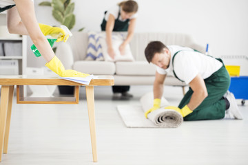 Man rolling carpet while cleaning