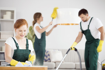 Women dusting and man vacuuming