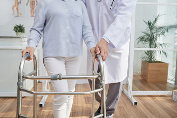 Close-up shot of unrecognizable physiotherapist explaining patient how to use front-wheeled walker, interior of modern office on background